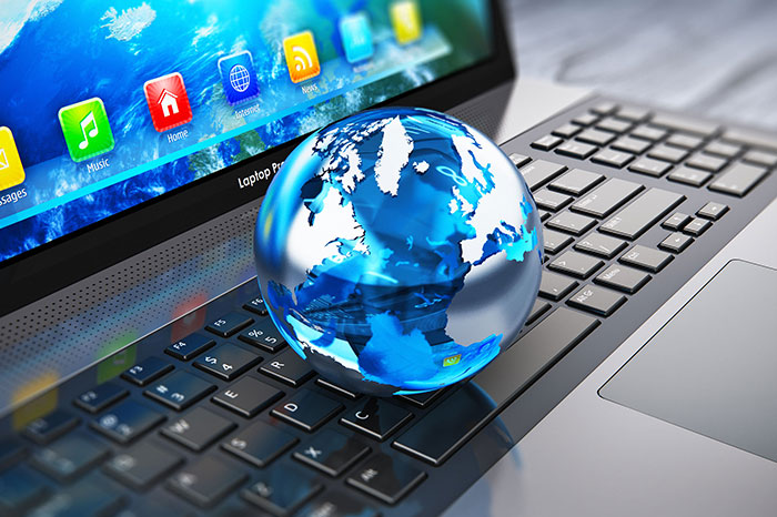 miniature globe sitting on laptop