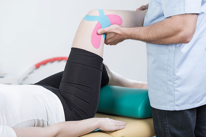 doctor rehabbing patients knee